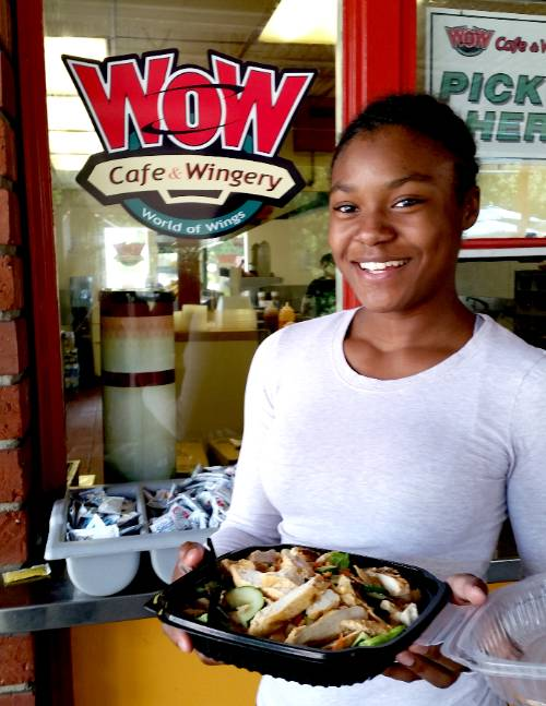 A student holds a salad from WOW cafe.