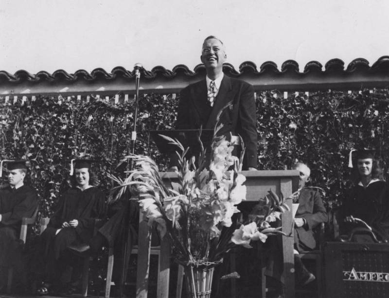 "Mt. SAC's first president, Dr. George Bell, at the college's first graduation in 1947, reads a telegram from California Governor Earl Warren: ""Thought you and your graduates might be interested to know I am today signing Assembly Bill 1904 making it possible for you to acquire the present site as a permanent home for Mount San Antonio College."""