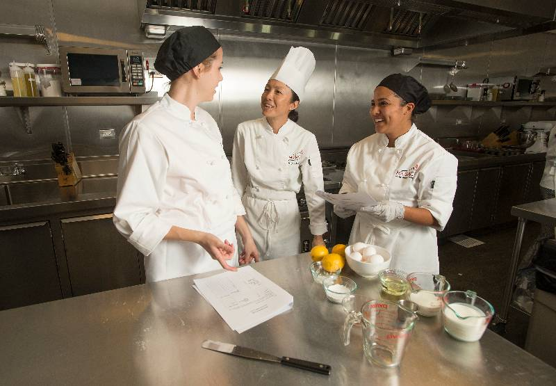 A professor discusses culinary management with students in their kitchen laboratory.