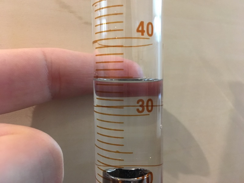 Volume reading on graduated cylinder with object and contrast for measurement