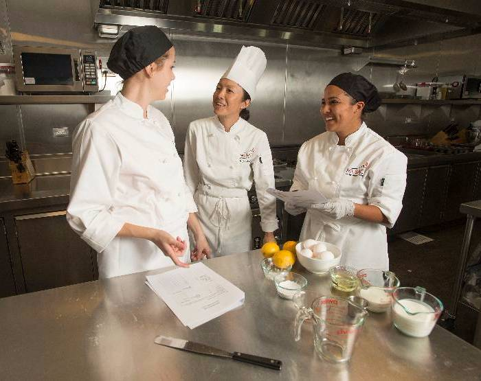 Professor Mee Shum works with culinary students. Some certificate programs only take one semester to complete