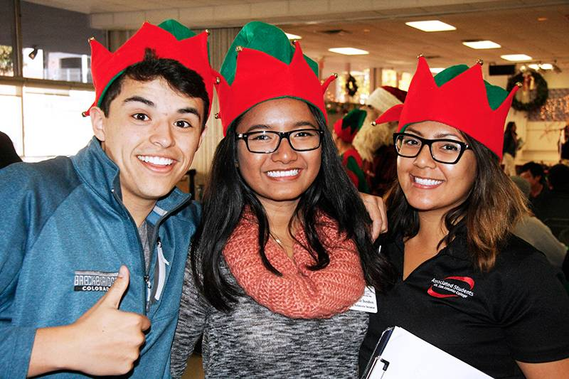 three students at the associated student's holiday celebration
