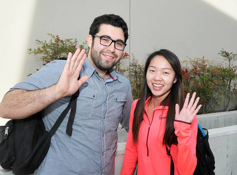 two students waving