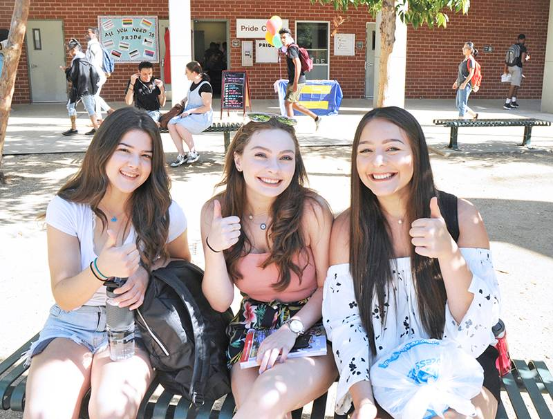 Three students smiling and giving the thumbs up.