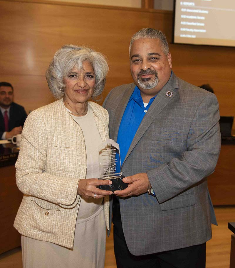 Board President Laura Santos awards Mario Barragan