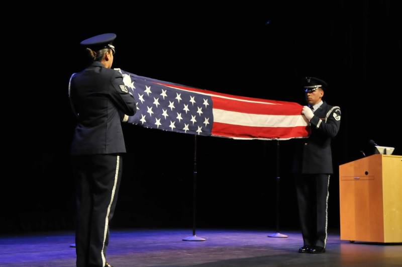 Air force representatives hold a flag folding ceremony