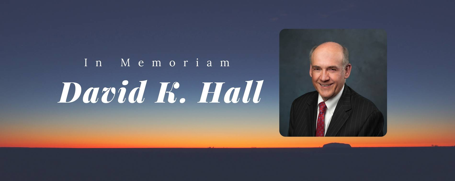 A sunset with an image of Trustee David Hall