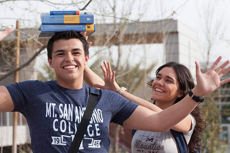 student balancing books on his head