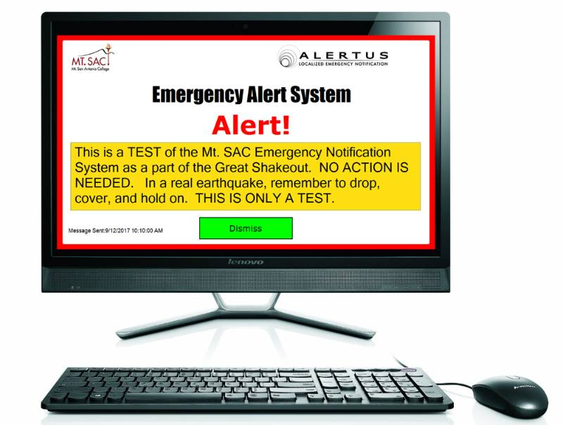 "A computer with a desktop notification on its screen saying ""Emergency Alert System."""