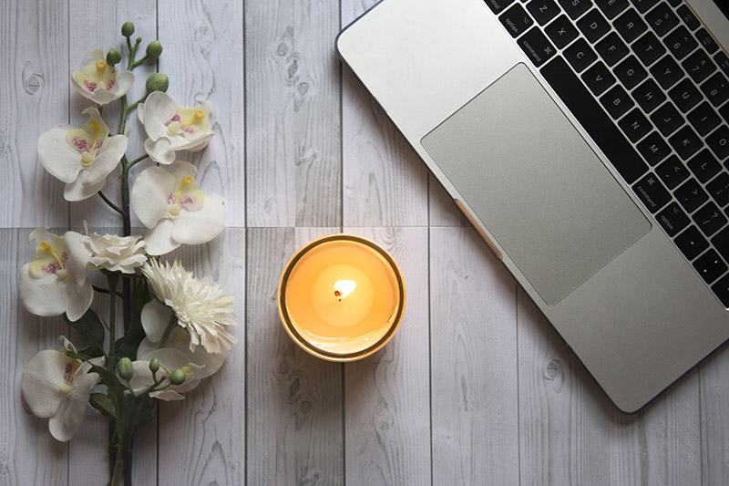 Candle, flowers and laptop