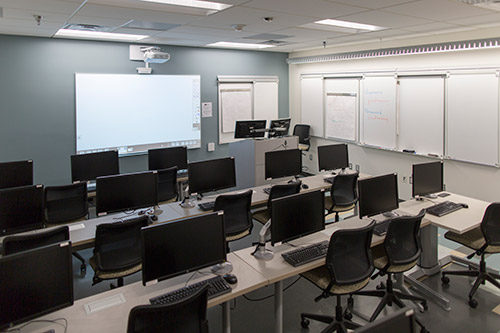 Computer classroom with multiple computers and projector