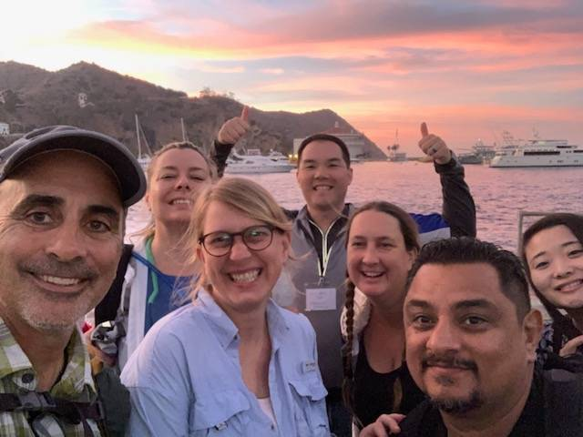Seven faculty take a group selfie with sunset behind them