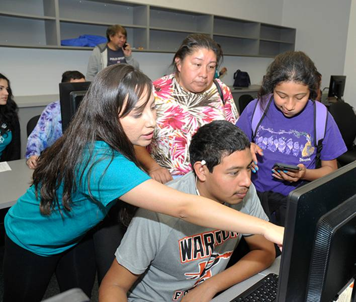 Staff helping students at computer
